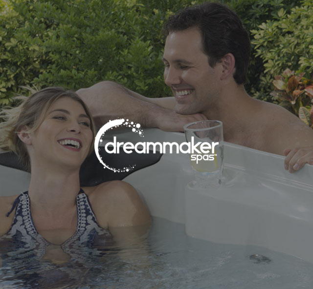 Couple enjoying a DreamMaker spa with logo | Pool and Spa Superstore Inc.